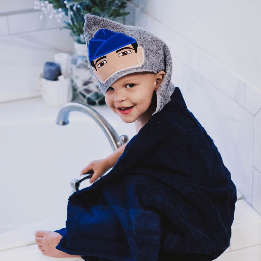 An Air Force brat sitting on the edge of a bathtub wrapped in a hooded towel with an Air Force man embroidered on the hood.