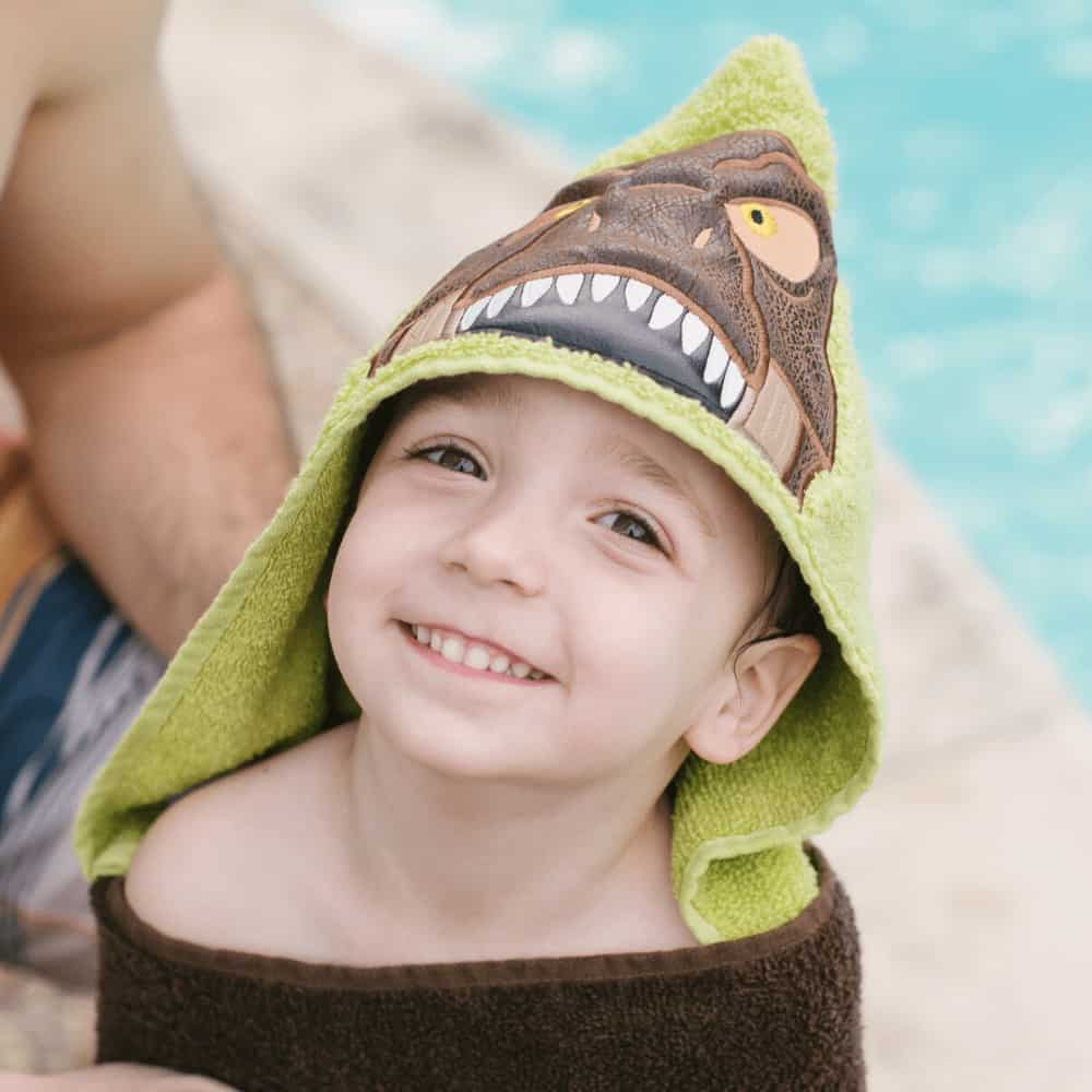 A little boy by the pool wearing a hooded towel with a T-rex dinosaur embroidered on the hood made by Kidderbug Kreations.