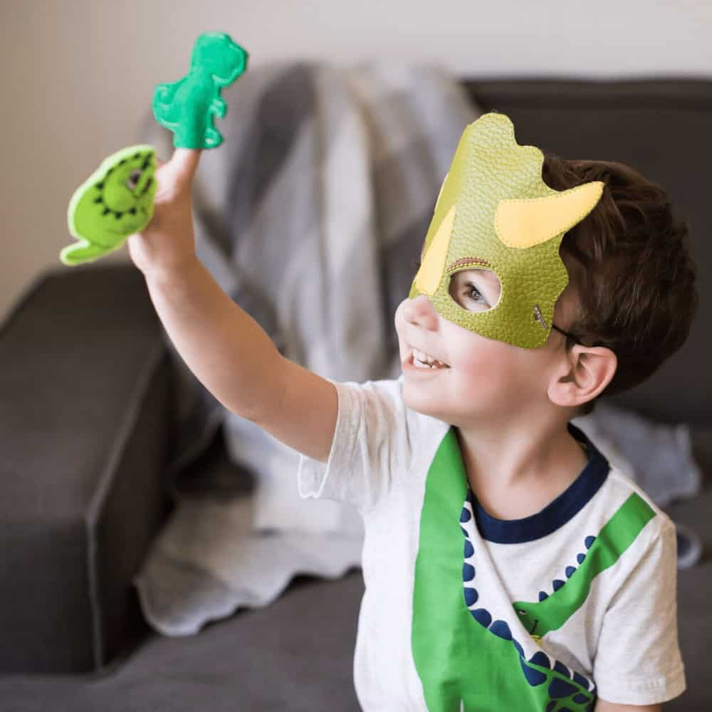 Little boy doing imaginative play while wearing a dinosaur mask and playing with dinosaur finger puppets.