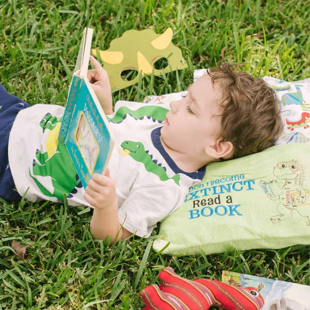 Little boy reading a book while lying on his dinosaur reading pillow from Kidderbug Kreations outside in the grass.
