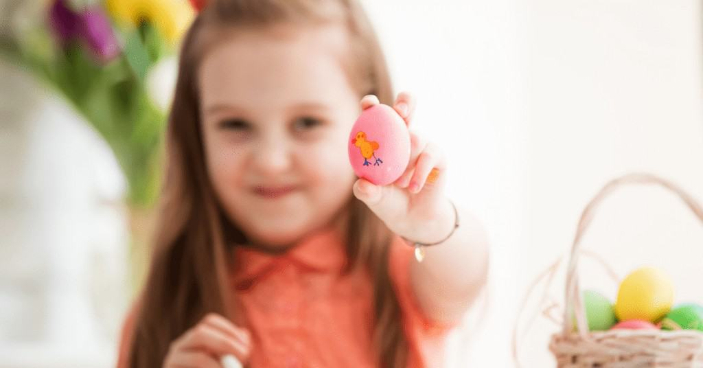 A little girl holding up an egg she decorated as a fun Easter activity for kids.
