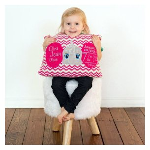 Little girl holding a pillow embroidered with an elephant face which has 3D ears embroidered with her birth stats.