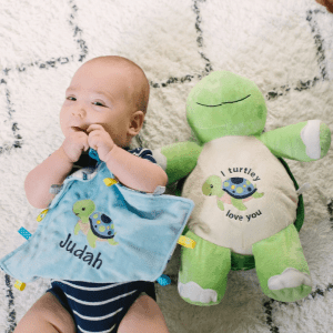 Baby with personalilzed stuffed turtle and custom sensory blanket