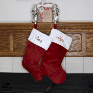 2 red Christmas stockings personalized with names embroidered on the white cuff and hanging by a fireplace.
