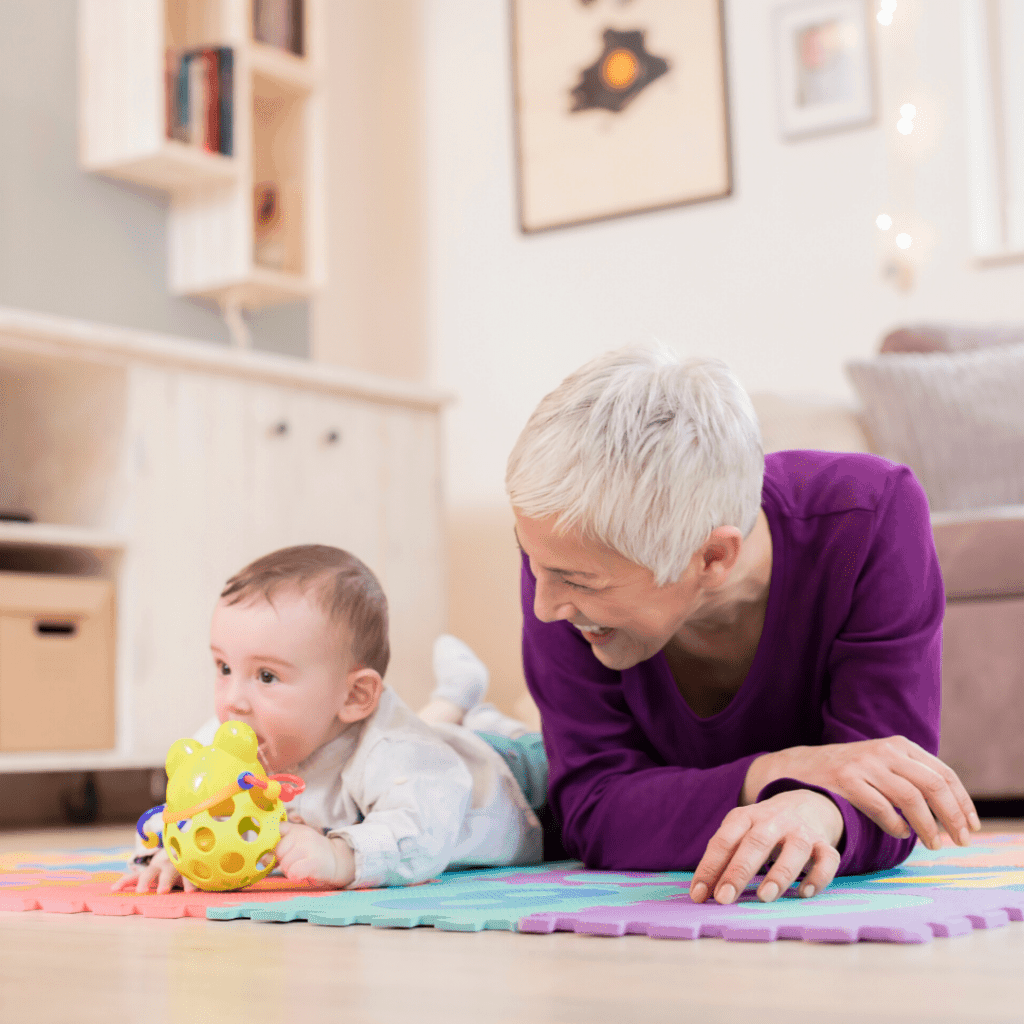 Grandma playing on the floor with her grandchild after using the safety checklist to be sure her home is baby proofed.