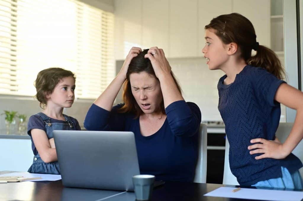 2 kids by the side of a stressed mom at her computer looking for quarantine activities for kids in order to work from home.