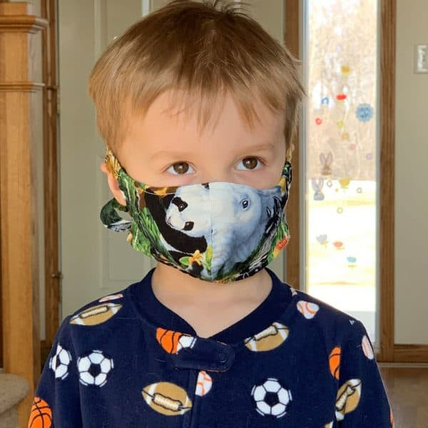 Little boy wearing a cotton fabric face mask with ties and a pocket for a filter to help prevent the spread of germs.