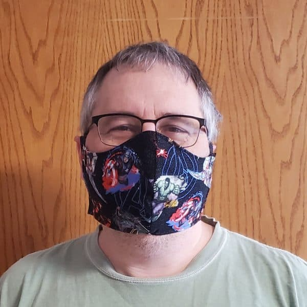 Man wearing a cotton fabric face mask with ties and a pocket for a filter to help prevent the spread of germs.