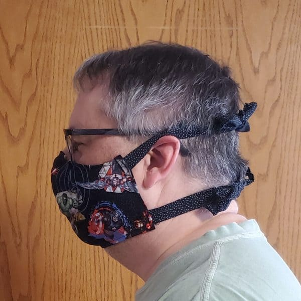 Side view of a man wearing a cotton fabric face mask with ties and a pocket for a filter to help prevent the spread of germs.