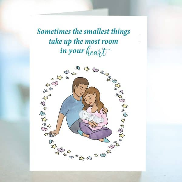 Miscarriage card with parents holding a baby that appears transparent. Butterflies and stars surround the family.