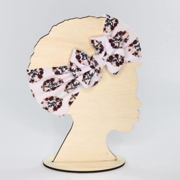 """The Child of God headwrap bow is white with burgundy flowers and """"Child of God"""" written on it. A wonderful gift idea for any little girl."""