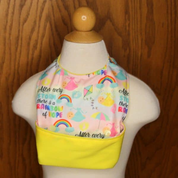 Rainbow baby designs on an adorable baby bib crumb catcher that keeps baby clean during mealtime. Unique snap design keeps spills contained.