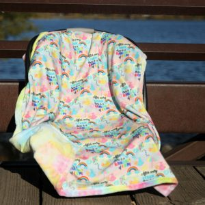 "Rainbow of hope baby blanket with exclusive fabric featuring rainbows and babies along with ""After every storm there is a rainbow of hope."""