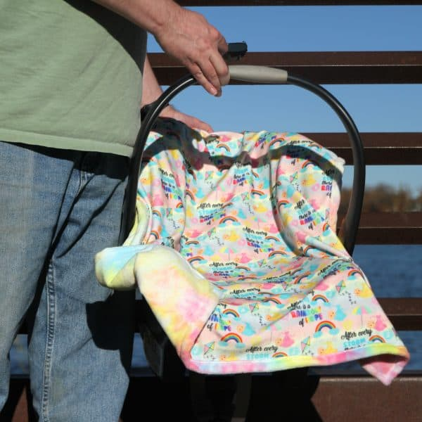 A man carrying a carseat covered with a rainbow of hope baby blanket exclusively available at Kidderbug Kreations.