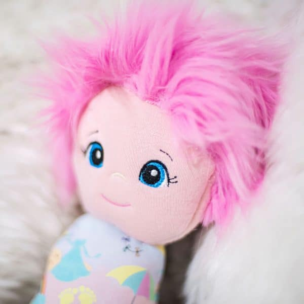 Close up of the face of the rainbow baby swaddle doll with pink hair from Kidderbug Kreations. It's the perfect little girl's first doll.