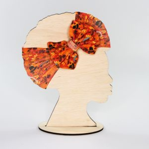 The fall/thanksgiving headwrap bow is orange and has pilgrim turkeys on it. A wonderful gift idea for any little girl.