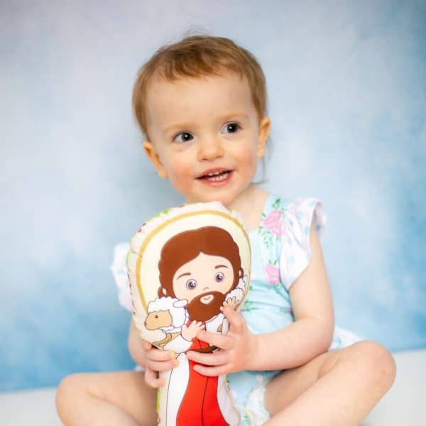 Little girl holding the Jesus the good shepherd fabric doll from Kidderbug Kreations.