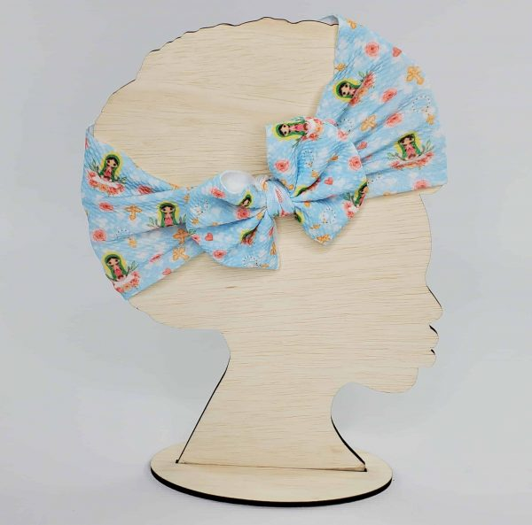 An Our Lady of Guadalupe Headwrap Bow featuring Our Lady of Guadalupe on a pale blue fabric with pink flowers and pink hearts.