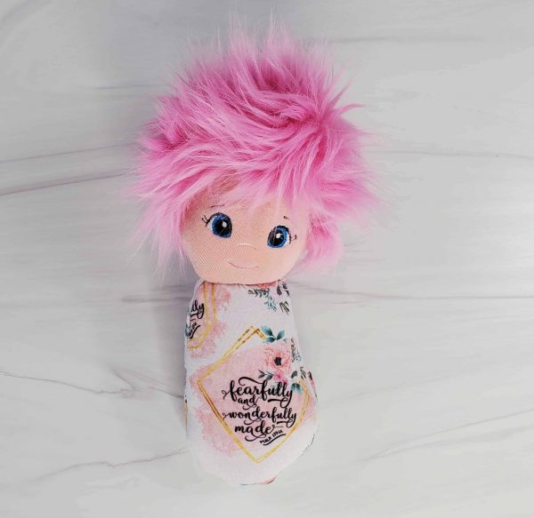 A Fearfully & Wonderfully Made Swaddle Doll with exclusive fabric from Kidderbug Kreations featuring soft pink and peach flowers with Psalm 139:14.