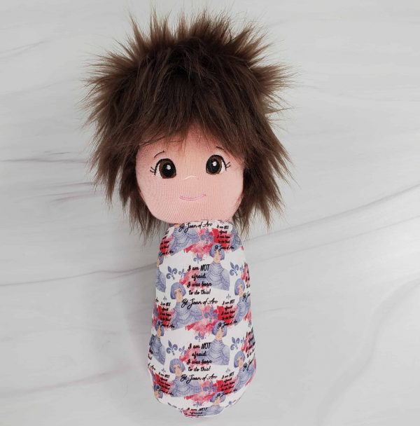 A St. Joan of Arc swaddle doll with exclusive fabric from Kidderbug Kreations featuring St. Joan of Arc with the phrase 'I was born to do this.'