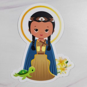 St. Kateri Tekakwitha vinyl sticker featuring her with a brown dress and blue robe. She's holding a cross and has lilies and a turtle with her.