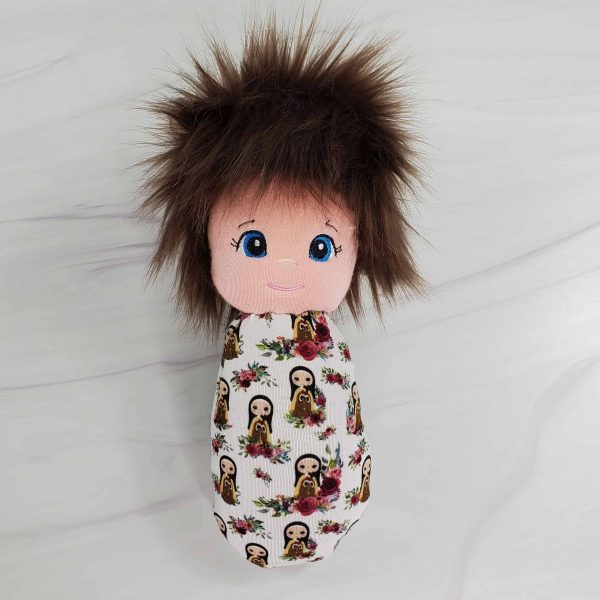 A St. Therese swaddle doll with exclusive fabric from Kidderbug Kreations featuring St. Therese with lots of flowers.