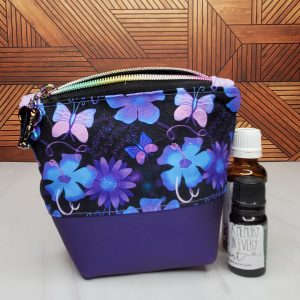 Essential oil bag with Alzheimer's awareness fabric featuring purple and blue flowers with pink and purple butterflies.