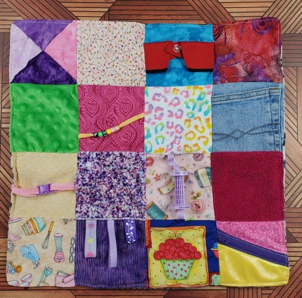 Fidget blanket for the elderly features various textured fabrics and activities to help Alzheimer's and dementia patients.