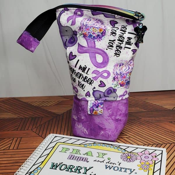 """A pen/marker stand-up bag with Alzheimer's awareness fabric featuring elephants, purple ribbons, and """"I will remember for you."""""""
